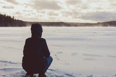 Una muchacha se sienta en la orilla de un lago del invierno imagen de archivo