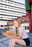 Una muchacha se sienta en pasos con el cuaderno Foto de archivo libre de regalías