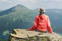 Una muchacha se sienta en una piedra y medita Fotografía de archivo