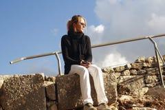 Una muchacha se sienta en una piedra y refleja Fotos de archivo