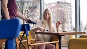 Una muchacha se sienta en una silla del café y paga su bebida almacen de metraje de vídeo
