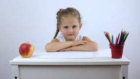Una muchacha se sienta en su escritorio y risas hasta que la lección comience almacen de video