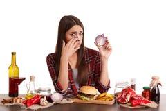 Una muchacha se sienta en una tabla con la comida y lleva a cabo una mitad de cebollas y de gritos de ella Aislado en blanco Fotografía de archivo libre de regalías