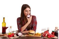Una muchacha, se sienta en una tabla con la comida y lleva a cabo una mitad de cebollas y de mordeduras él Aislado en blanco Fotografía de archivo libre de regalías