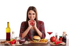 Una muchacha, se sienta en una tabla con la comida y los controles una mitad de una granada y sonríe Aislado en blanco Imagen de archivo libre de regalías