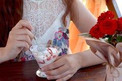 Una muchacha se sienta en una tabla en un café y come una cuchara con helado imagen de archivo