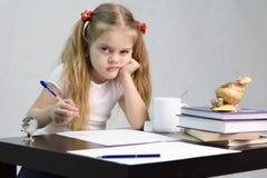 La muchacha escribe en un trozo de papel que se sienta en la tabla en la imagen del escritor Imagen de archivo libre de regalías