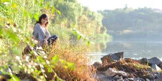 Una muchacha se sienta por el río Foto de archivo