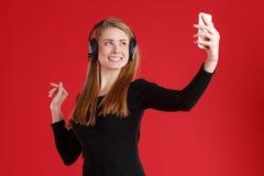 Una muchacha se vistió en auriculares en su cabeza, sonriendo y haciendo el selfie en un teléfono móvil En un fondo rojo imágenes de archivo libres de regalías