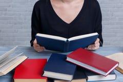 Una muchacha, sentándose en una tabla entre los libros y leyendo un libro con una cubierta roja foreground fotografía de archivo libre de regalías