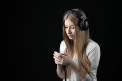 Una muchacha seria del adolescente en música que escucha en auriculares atados con alambre Imagenes de archivo