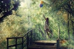 Una muchacha soñadora en un bosque con los globos Imágenes de archivo libres de regalías