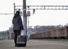 Una muchacha sola con una maleta negra se está colocando en la plataforma que espera el tren imagenes de archivo