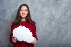 Una muchacha sonriente bonita joven en un suéter rojo contra el backgro imagenes de archivo