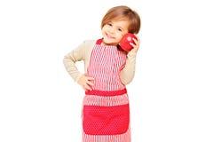 Una muchacha sonriente con el delantal que sostiene una manzana roja imagenes de archivo