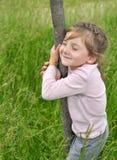 Una muchacha sonriente con ella los ojos cerró el abarcamiento de un tronco de árbol Foto de archivo