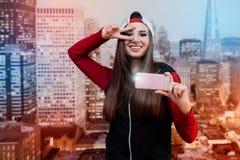Una muchacha sonriente con los ojos morados Vestido en negro con un suéter rojo y un casquillo dados vuelta al revés Sí mismo fot Fotografía de archivo libre de regalías