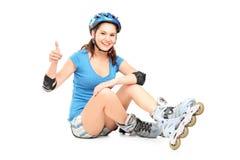 Una muchacha sonriente con los pcteres de ruedas que dan un pulgar para arriba Foto de archivo