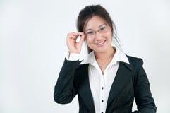 Una muchacha sonriente del asunto en vidrios Foto de archivo libre de regalías