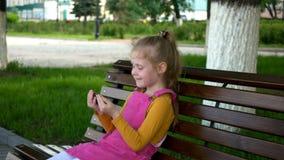 Una muchacha sonriente una edad preescolar, utiliza el teléfono al aire libre en el parque D?a de verano asoleado almacen de metraje de vídeo