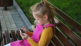 Una muchacha sonriente una edad preescolar, utiliza el teléfono al aire libre en el parque D?a de verano asoleado almacen de video