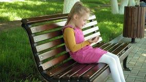 Una muchacha sonriente una edad preescolar, utiliza el teléfono al aire libre en el parque D?a de verano asoleado metrajes