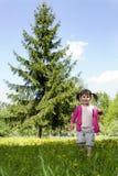 Una muchacha sonriente en el campo del diente de león Foto de archivo libre de regalías