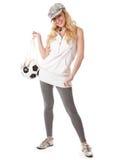 Una muchacha sonriente en un casquillo con una bola del balompié Imágenes de archivo libres de regalías