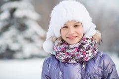 Una muchacha sonriente en un sombrero y una bufanda en invierno Imagen de archivo libre de regalías