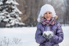 Una muchacha sonriente en un sombrero y una bufanda que juegan con las bolas de nieve Imágenes de archivo libres de regalías