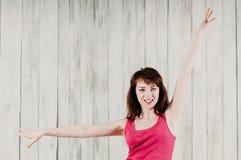 Una muchacha sonriente en un top rosado, haciendo ejercicio de los aeróbicos imagenes de archivo