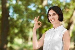 Una muchacha sonriente en una camisa blanca en un fondo de la naturaleza Muchacha hermosa que hace una muestra del ` de la AUTORI Fotografía de archivo