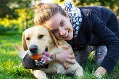 Una muchacha sonriente está jugando con su perro Fotografía de archivo