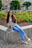 Una muchacha sonriente hermosa que se sienta al lado de una cama de flor al aire libre a Fotografía de archivo libre de regalías