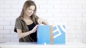 Una muchacha sonriente joven abre un regalo de la caja Imagen de archivo