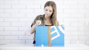 Una muchacha sonriente joven abre un regalo de la caja Fotografía de archivo