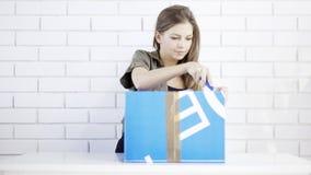 Una muchacha sonriente joven abre un regalo de la caja Foto de archivo