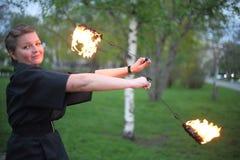 Una muchacha sonriente muestra una demostración del fuego. Fotos de archivo libres de regalías