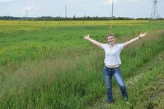 Una muchacha sonriente que se coloca al borde del campo Fotos de archivo libres de regalías