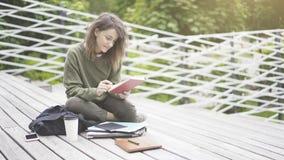 Una muchacha sonriente se está sentando en las escaleras que lee un libro al aire libre Fotografía de archivo libre de regalías