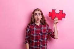 Una muchacha sorprendida, controles un rompecabezas grande de la mano aumentada con la boca abierta En un fondo rosado Fotos de archivo libres de regalías