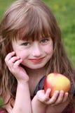 Una muchacha sostiene la manzana Imagenes de archivo
