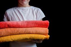 Una muchacha sostiene las toallas en sus manos imagenes de archivo