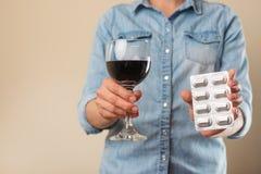 Una muchacha sostiene una píldora con una copa de vino, una prohibición en las drogas para el alcohol, la opción del tratamiento  imagen de archivo libre de regalías