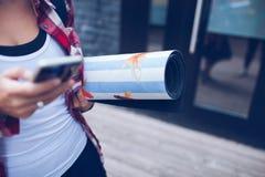 Una muchacha sostiene una estera de la yoga disponible Fotos de archivo