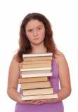 Una muchacha sostiene una pila de libros Fotografía de archivo libre de regalías