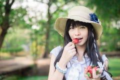Una muchacha tailandesa asiática linda con la ropa vintage está comiendo el strawber Foto de archivo libre de regalías