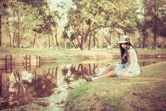 Una muchacha tailandesa asiática linda es relajante cerca de la charca Imagenes de archivo