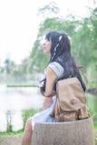 Una muchacha tailandesa asiática linda es relajante en un asiento de la roca que deja su th Fotos de archivo