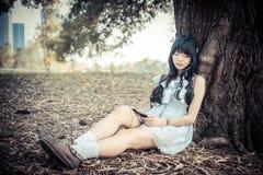 Una muchacha tailandesa asiática linda se está inclinando en un tronco de árbol que duerme mientras que Fotografía de archivo